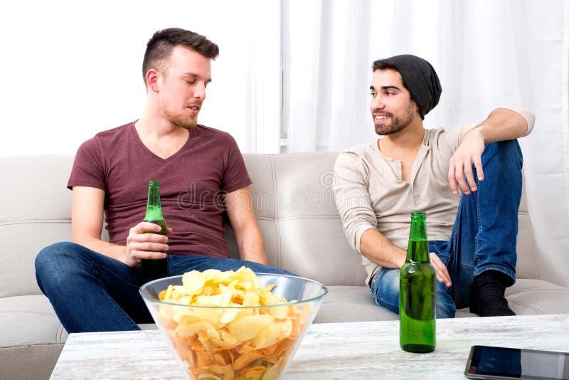 Dos amigos que tienen una conversación en la sala de estar foto de archivo