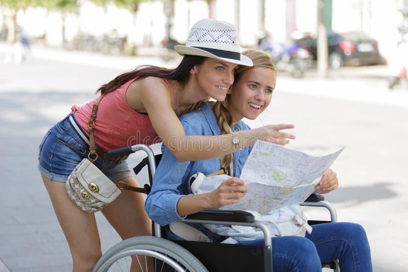 Dos amigos que visitan la ciudad extranjera una que se sienta en silla de ruedas fotos de archivo libres de regalías