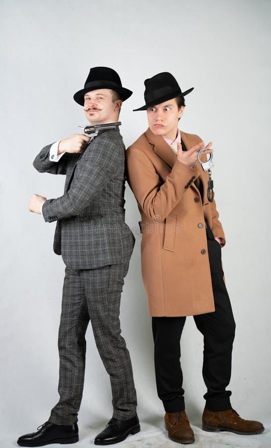 Dos amigos se vistieron en ropa del vintage y representan detectives y a espías retros en estilo clásico inglés en un fondo blanc imagen de archivo