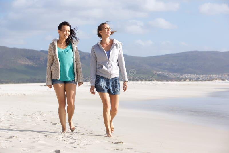 Dos amigos sonrientes de las mujeres que caminan en la playa junto imagen de archivo libre de regalías
