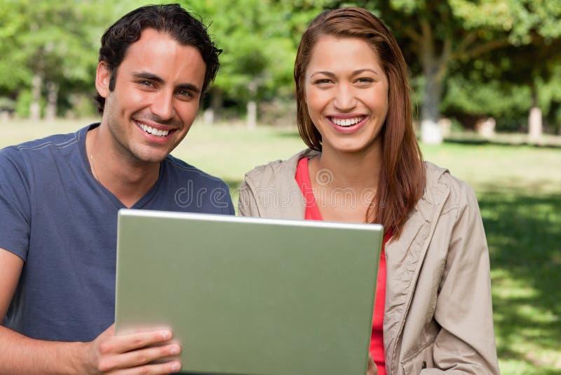 Dos amigos sonrientes que anticipan como sostienen una tablilla fotos de archivo libres de regalías