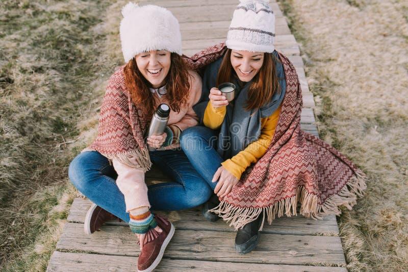 Dos amigos tienen un ajuste de la risa mientras que beben el caldo que se sienta en el medio del prado imagen de archivo