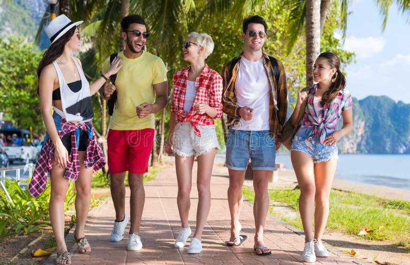Dos amigos tropicais das palmeiras da praia do grupo dos jovens férias de verão faladoras de passeio do mar do feriado imagens de stock royalty free