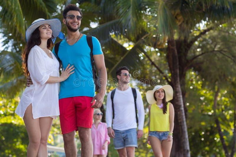 Dos amigos tropicais das palmeiras do parque do grupo dos jovens férias de verão faladoras de passeio do feriado imagem de stock royalty free
