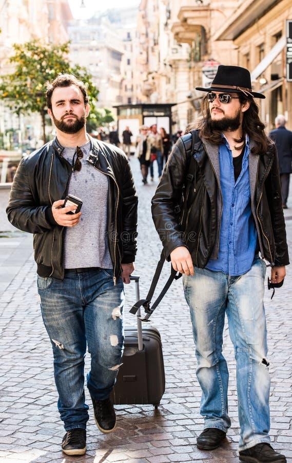 Dos amigos, turistas están buscando para su hotel en el smartphone, fotografía de archivo