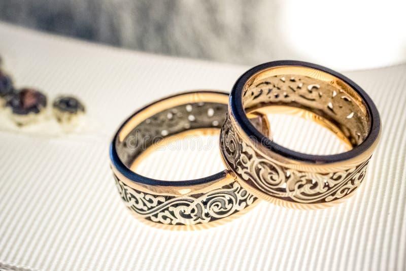 Dos anillos de bodas con diseño raro en la cinta amplia blanca imágenes de archivo libres de regalías
