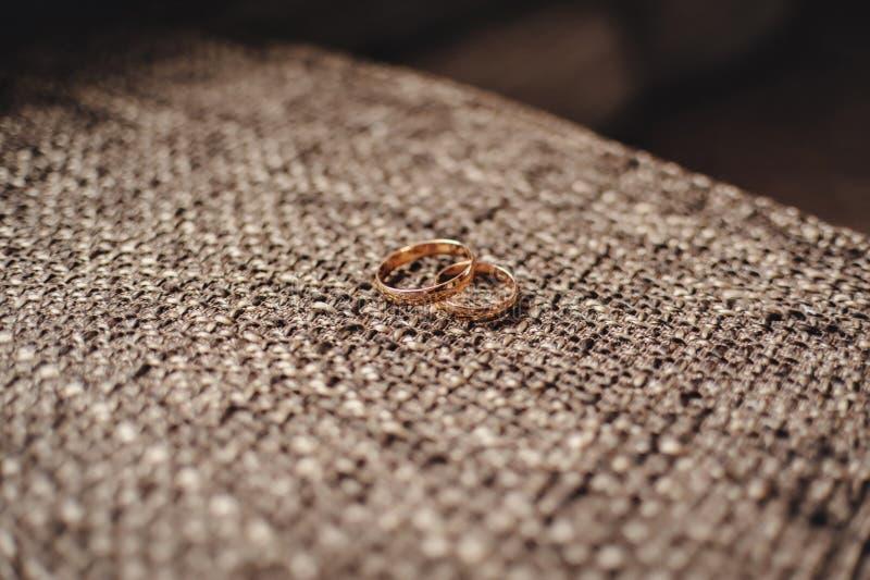 Dos anillos de bodas del oro en un fondo marrón con el despido imagenes de archivo