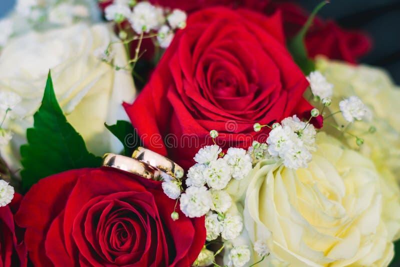 Dos anillos de bodas del oro mienten en el ramo nupcial integrado por las rosas blancas y rojas imagen de archivo