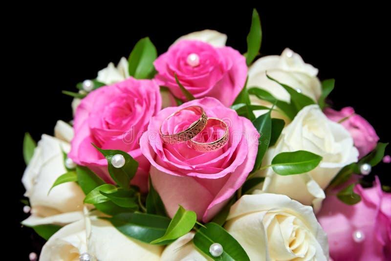 Dos anillos de bodas en el ramo colorido de rosas blancas y rosadas en el fondo negro, cierre para arriba imagen de archivo