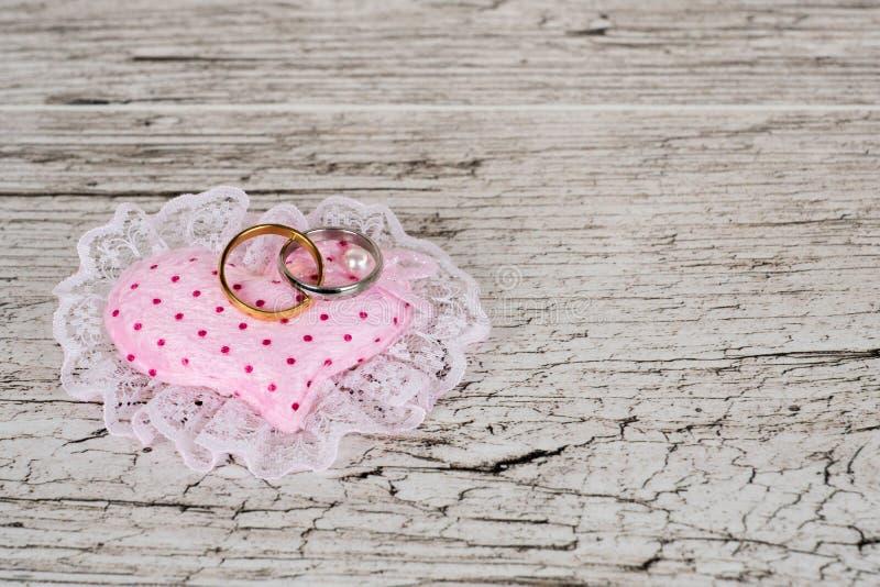 Dos anillos de bodas en la almohada rosada del corazón foto de archivo