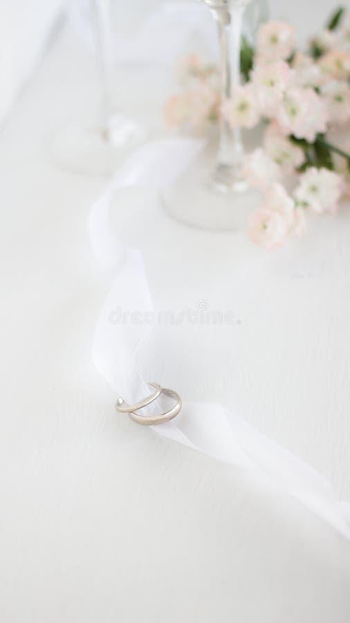 Dos anillos de bodas en la cinta blanca Fondo ligero de la falta de definici?n de flores y de vidrios del champane imagenes de archivo