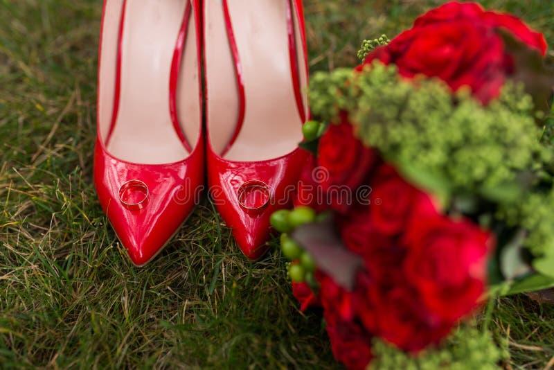 Dos anillos de bodas de oro mienten en los zapatos femeninos de la moda roja en hierba verde boda foto de archivo