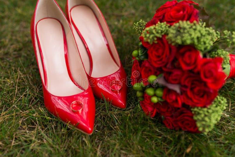 Dos anillos de bodas de oro mienten en los zapatos femeninos de la moda roja en hierba verde boda imagen de archivo libre de regalías