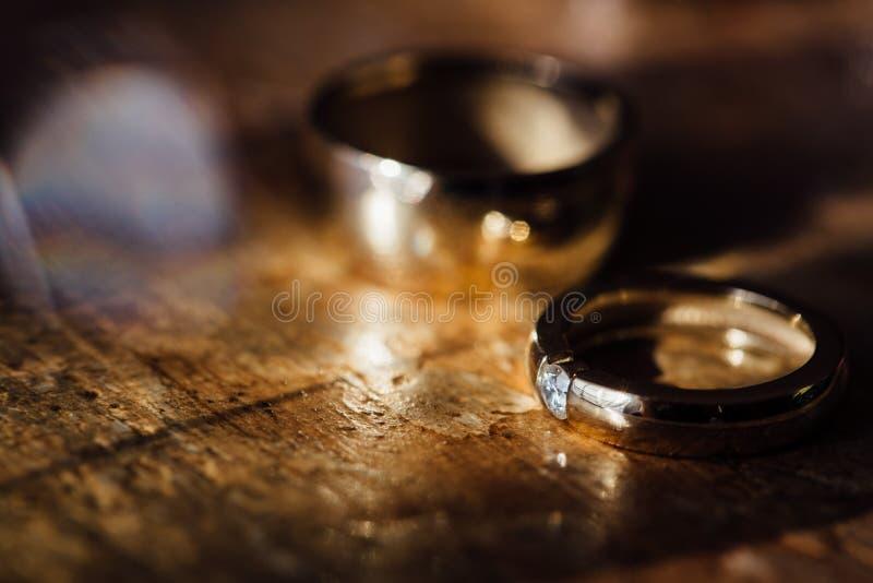 Dos anillos de bodas de oro y pendientes hermosos en un fondo de madera imagen de archivo libre de regalías
