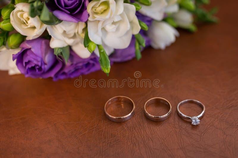 Dos anillos de bodas y anillos de compromiso de oro con un diamante en fondo marrón imagen de archivo libre de regalías