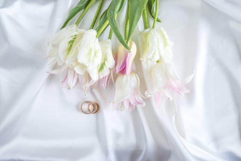 Dos anillos de bodas y ramos de tulipanes blancos imagen de archivo