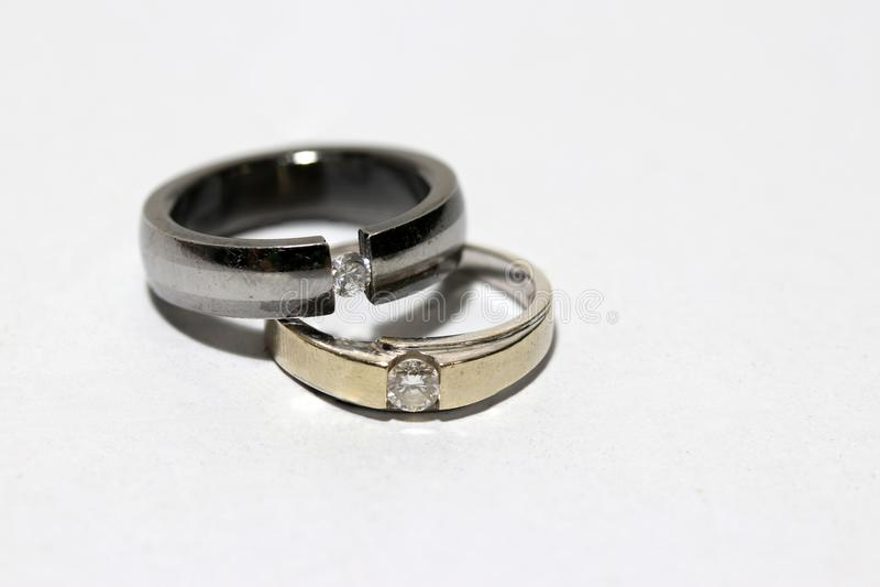 Dos anillos de diamante apilados en el fondo blanco foto de archivo