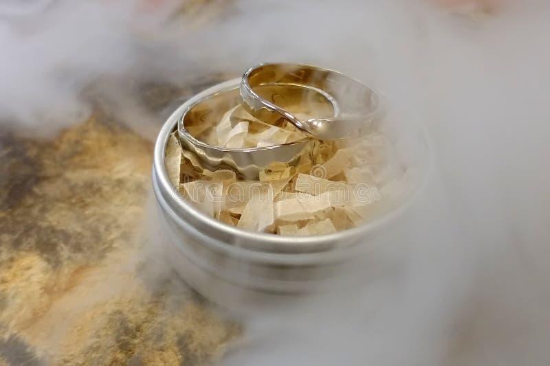 Dos anillos de oro blanco est?n en una caja redonda del metal Soporte en una tabla en el humo imagenes de archivo