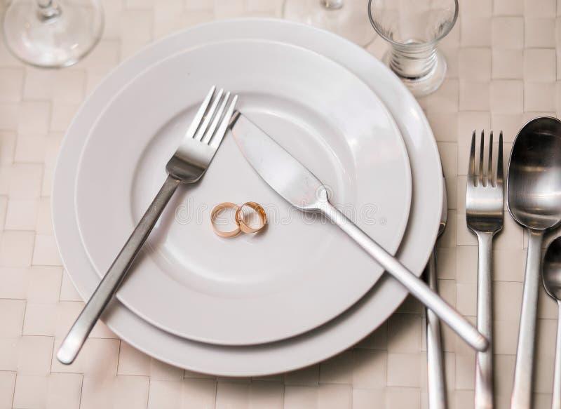 Dos anillos en una placa con la porción bifurcan, cucharean, cuchillo El concepto de una celebración de la boda en el banquete, r imagenes de archivo