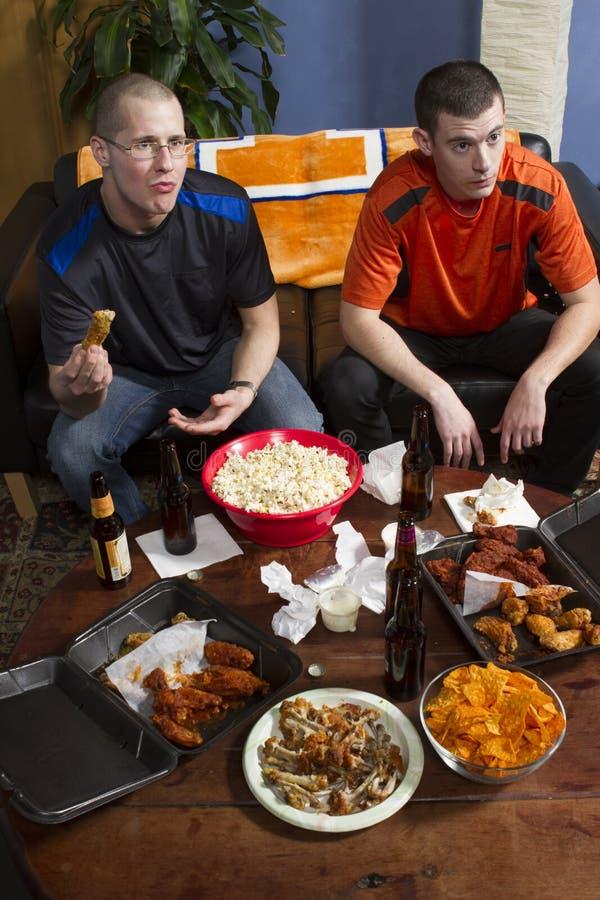 Dos ansiosos mientras que la observación se divierte el juego en la TV, vertical imagen de archivo
