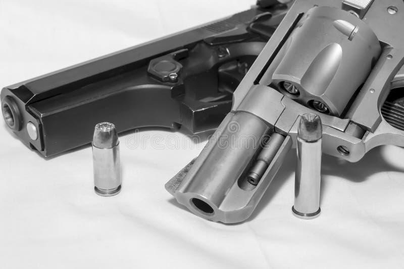 Dos armas de mano, una pistola de 40 calibres y un revólver de 357 botellas dobles junto con una bala para cada uno imágenes de archivo libres de regalías