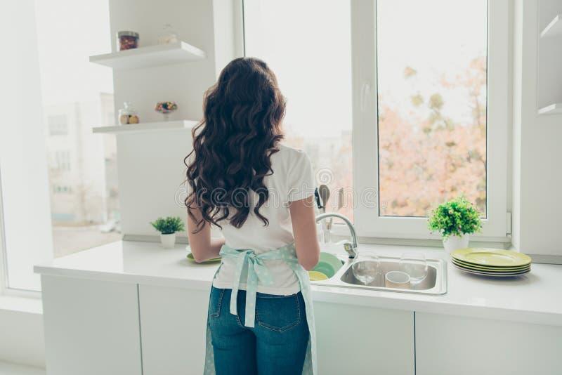Dos arrière derrière le portrait de vue de elle elle plats de lavage de gentille belle femme au foyer aux cheveux ondulés attiran photos stock