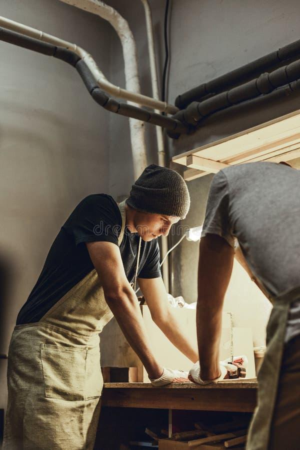 Dos artesanos que se colocan cerca del banco de trabajo foto de archivo
