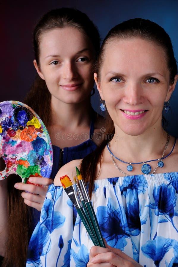 dos artistas con las pinturas y los cepillos adentro entregan el fondo negro fotografía de archivo