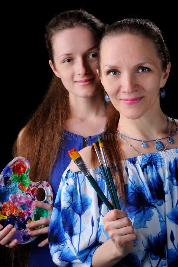 dos artistas con las pinturas y los cepillos adentro entregan el fondo negro imagen de archivo libre de regalías