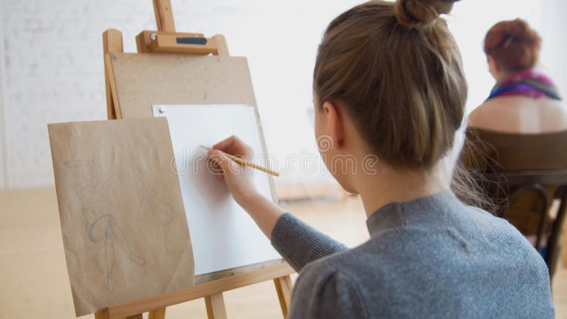 Dos artistas de sexo femenino que bosquejan el modelo en clase de dibujo brillante foto de archivo libre de regalías