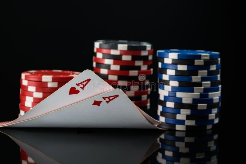 Dos as rojos en tarjetas del póker contra la perspectiva de las participaciones del póker fotos de archivo