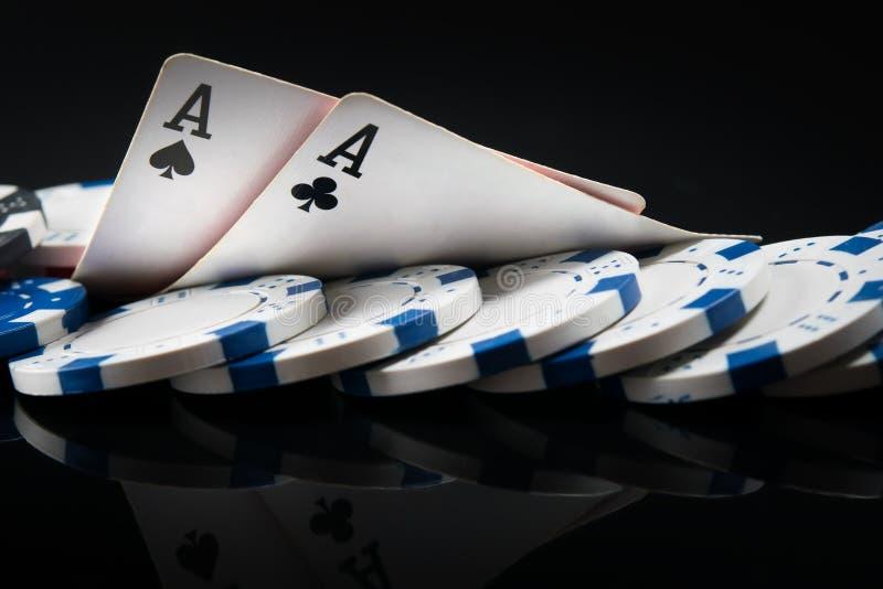 Dos as y fichas de póker, en un fondo negro con los mappings fotos de archivo libres de regalías