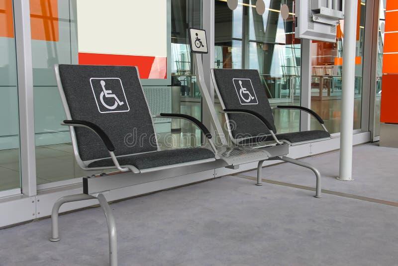 Dos asientos para las personas con discapacidades en pasillo moderno del aeropuerto fotos de archivo