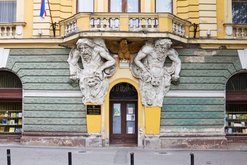 Dos atlantes en la fachada de la biblioteca pública en Subotica imagenes de archivo