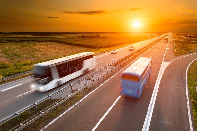 Dos autobuses en la carretera en la falta de definición de movimiento fotos de archivo libres de regalías