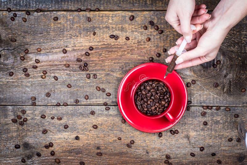 Dos av kaffe med koppen och injektionssprutan arkivfoto