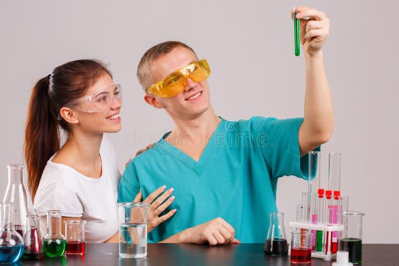 Dos ayudantes de laboratorio El individuo está sosteniendo un frasco con un líquido verde y lo está mirando foto de archivo libre de regalías