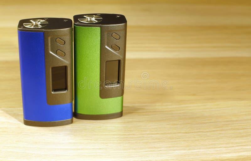 Dos azules y dispositivos verdes del boxmod para vaping el cigarrillo electrónico en el cierre de madera de la superficie para ar imagenes de archivo