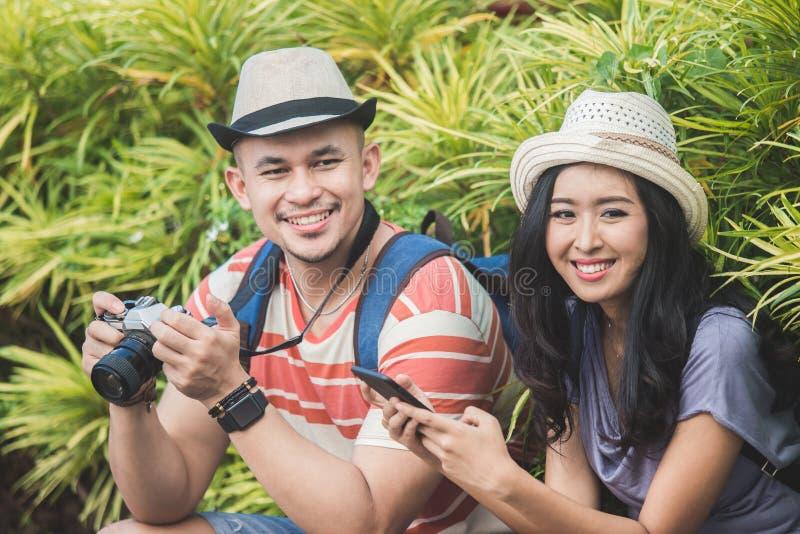 Dos backpackers con el sombrero del verano que sonríen a la cámara imágenes de archivo libres de regalías