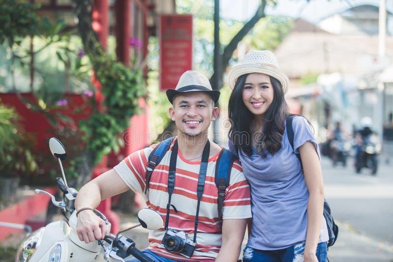 Dos backpackers con el sombrero del verano que sonríen a la cámara mientras que se sienta imagen de archivo libre de regalías