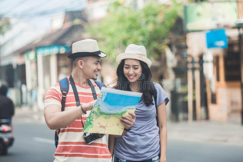 Dos backpackers jovenes que buscan la dirección en mapa de ubicación mientras que imagen de archivo