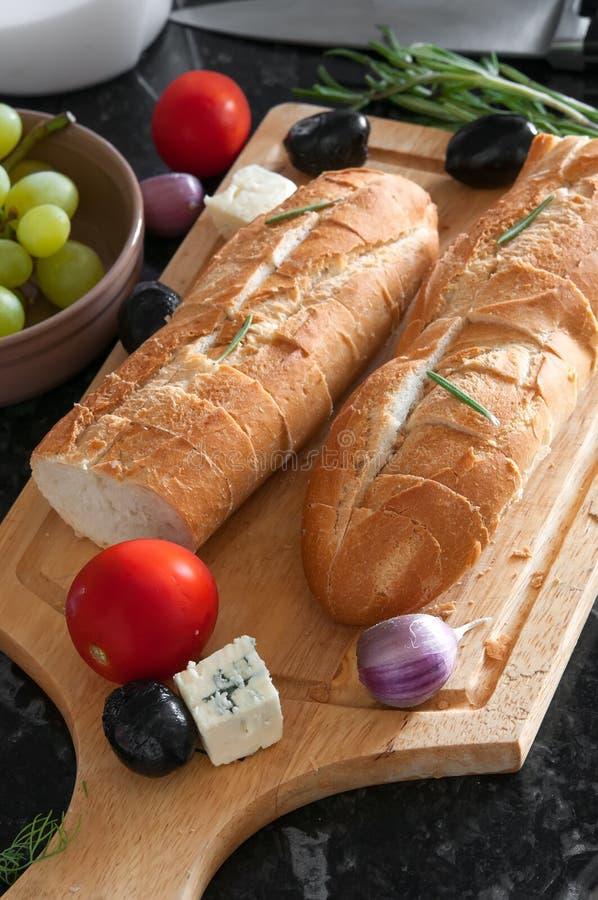 Dos baguettes e ingredientes del pan en tabla de cortar de madera fotos de archivo