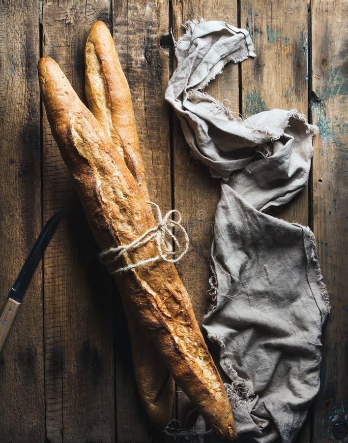 Dos baguettes franceses en fondo de madera rústico áspero imagen de archivo