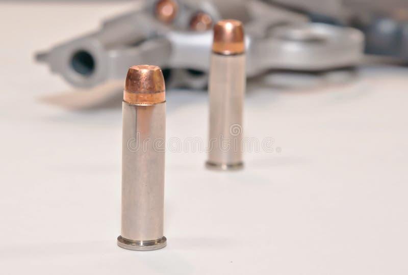 Dos balas delante de un revólver cargado imagen de archivo libre de regalías