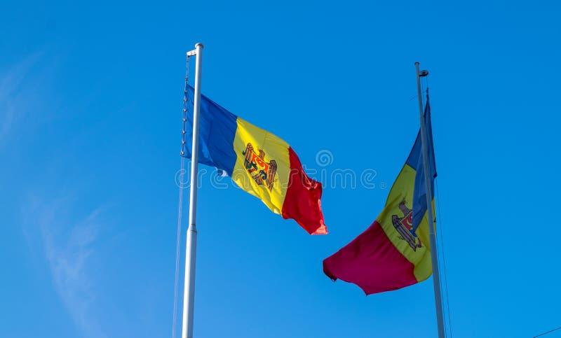 Dos banderas de Moldavia agitan en el cielo azul imagenes de archivo