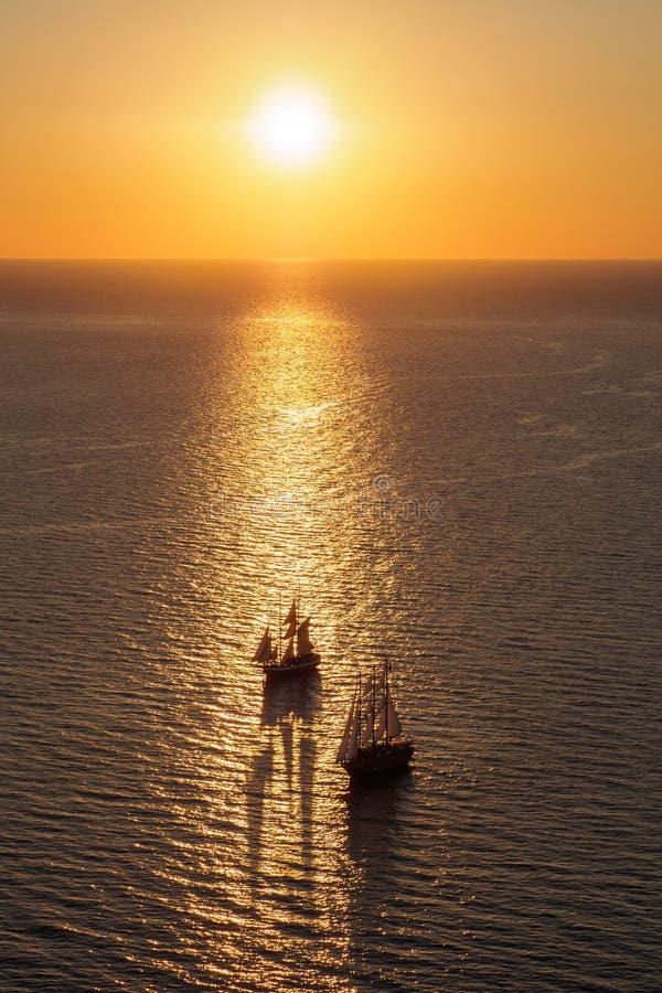 Dos barcos en la superficie del mar en la salida del sol imagen de archivo libre de regalías