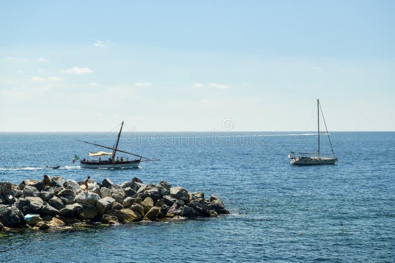 Dos barcos que se persiguen cerca de la ciudad de Manarola fotos de archivo libres de regalías