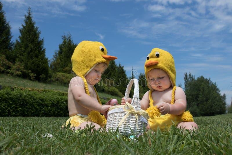 Dos bebés infantiles en el pollo de Pascua visten jugar con los huevos fotos de archivo