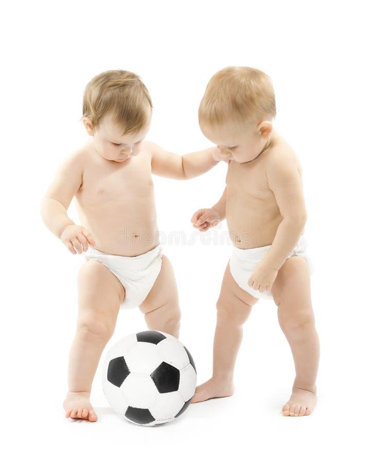 Dos bebés que juegan el balón de fútbol sobre blanco fotos de archivo libres de regalías