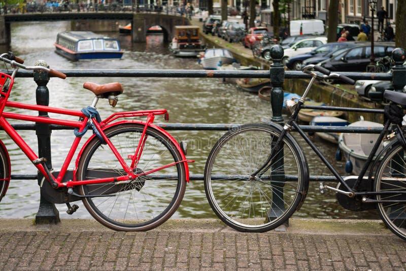 Dos bicicletas en un puente sobre un canal en Amsterdam, Países Bajos fotografía de archivo